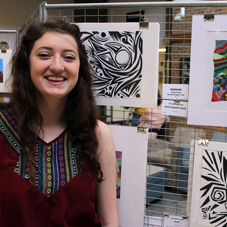students standing beside art work during art show