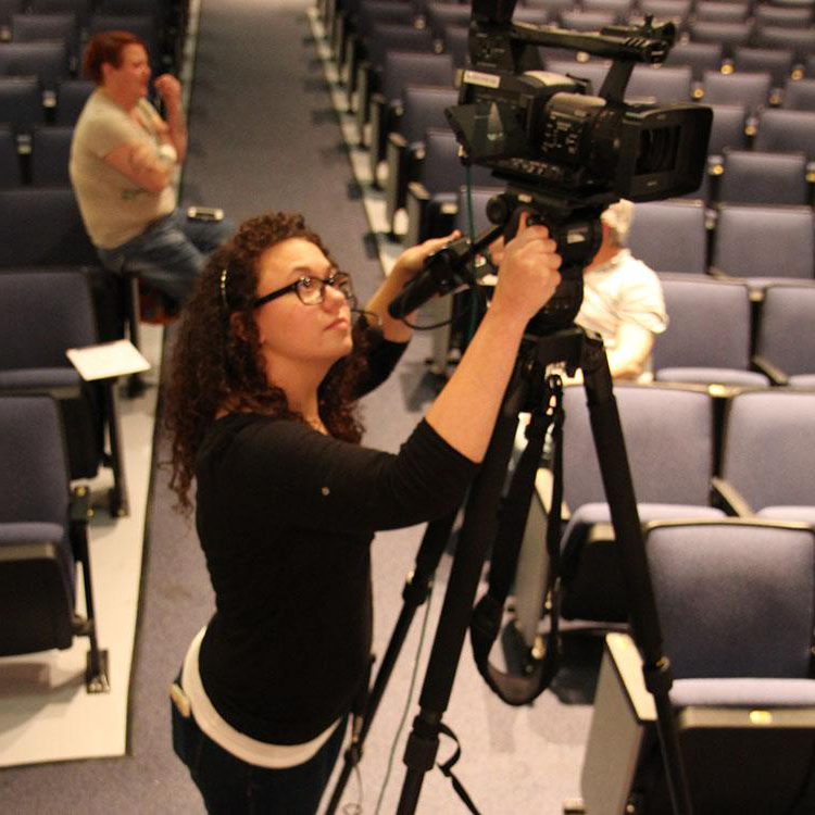 student filming with a video camera